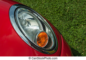 auto headlight on a red car with green grass background