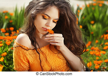 Beautiful Teenage Model girl smelling flower, over marigold...