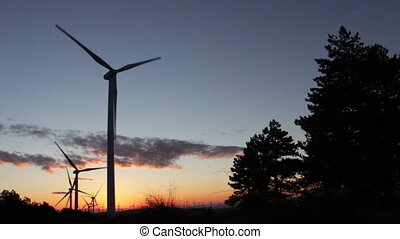 Windmills at Sunrise - Windmills rotating energetically in...