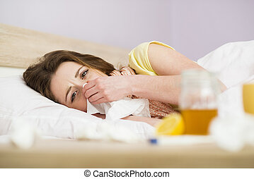 Sick woman lying in bed with high fever. She has cold and...