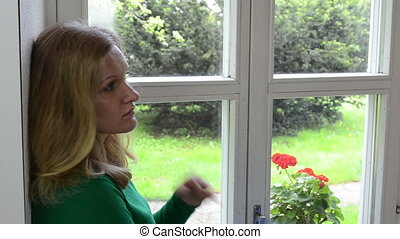 blond girl window sill - Blond woman play with long hair...