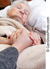 Home care - Woman holding elderly hands at home