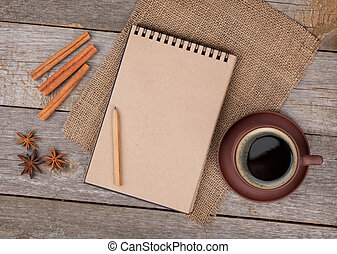 Blank notepad with coffee cup and spices on wooden table -...