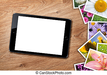 Tablet with blank screen and stack of printed pictures...