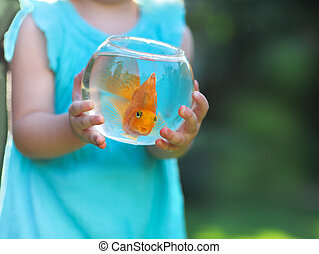 Little baby girl holding a fishbowl with a goldfish on a...