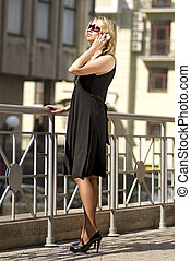 rich city woman talking by mobile phone on the street