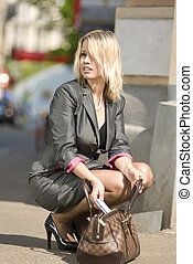 thoughtless city woman - beautiful blond woman siting and...