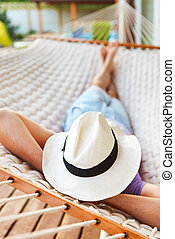Man in hat in a hammock on a summer day - Lazy time. Man in...