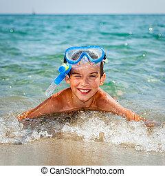 Boy on a beach - Happy boy wearing snorkeling gear lying in...