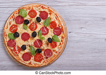 whole pizza with salami, tomato, cheese, olives and basil