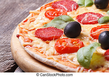 pizza with salami, tomato, olives and basil close-up