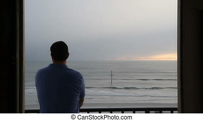 Man watching the sunrise on Daytona Beach Fl