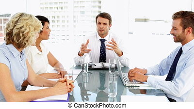Business people listening to their boss during meeting in...