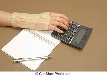 woman's hand with carpal tunnel syndrome doing calculations...