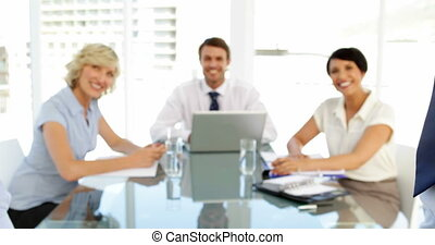 Business people smiling at camera during a meeting in the...