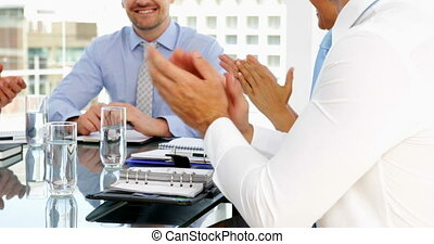 Business people applauding their boss during meeting in the...