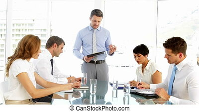 Businessman standing and speaking during meeting in the...