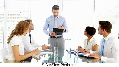 Businessman standing and talking during meeting in the...