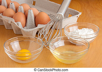 Eggs, Bowls and a Whisk - Separated cracked eggs in glass...