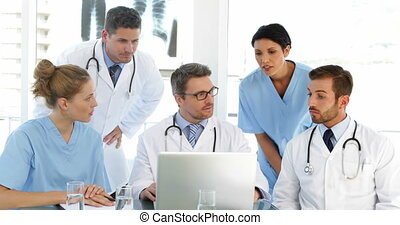 Doctor chatting with his staff during a meeting at the...