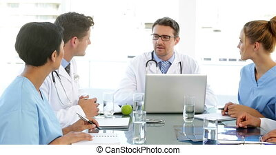 Doctor talking with his staff during a meeting at the...