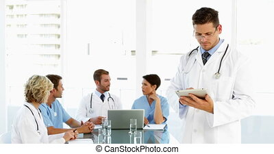 Thoughtful doctor using tablet with staff talking behind him...
