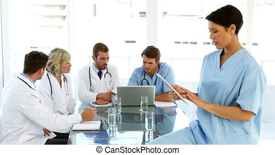 Thoughtful surgeon using her tablet with staff talking...