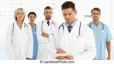 Serious doctor writing on clipboard while staff are standing...