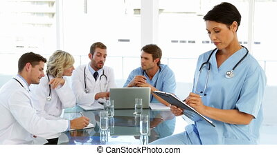 Thoughtful surgeon writing on clipboard