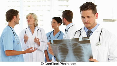 Serious doctor holding xray while staff are standing behind...