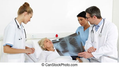 Doctors explaining xray to patient in bed at the hospital