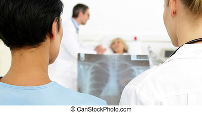 Doctors discussing xray in front of sick patient in bed at...