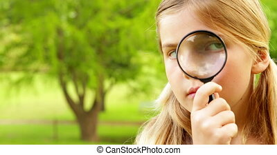 Cute little girl using magnifying glass in park on a sunny...