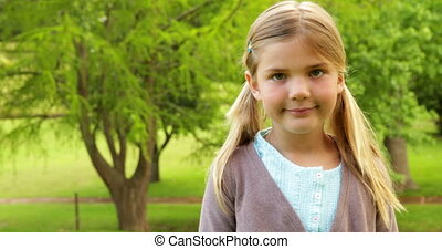 Cute little girl smiling and waving on a sunny day