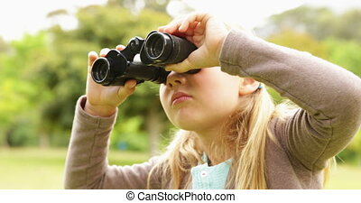Cute little girl using binoculars in park on a sunny day