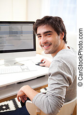 Young smiling man in front of computer