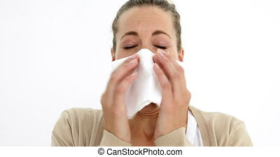 Beautiful sick woman sneezing using a tissue on white...