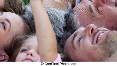 Multi generation family smiling and lying on ground in a...