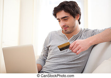 Young relaxed man paying online with credit card in sofa -...