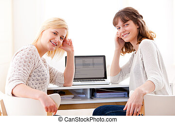 Two students girls working on a laptop - View of Two...