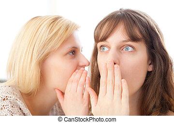 Blonde girl telling a secret to her best friend