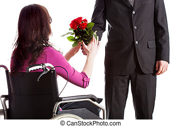 Fiancee on wheelchair - Man giving flowers to his woman on...