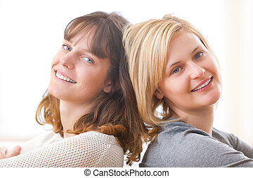 Best friends sitting on a sofa - View of 2 best friends on a...