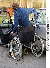 Disabled man getting in the car - Handicapped driver getting...