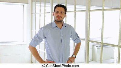 Content handsome man posing with hands on hips in the office