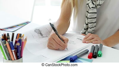 Focused young creative designer sketching ideas in creative...
