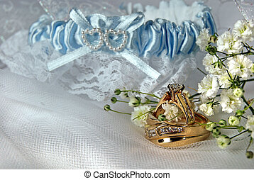 With This Ring - Wedding ring and garter on bridal tulle.