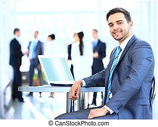 Happy young businessman using laptop in business building