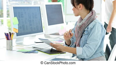 Cute creative designer working sitting at her desk in...