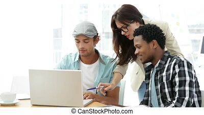 Employees working together on laptop at desk in creative...